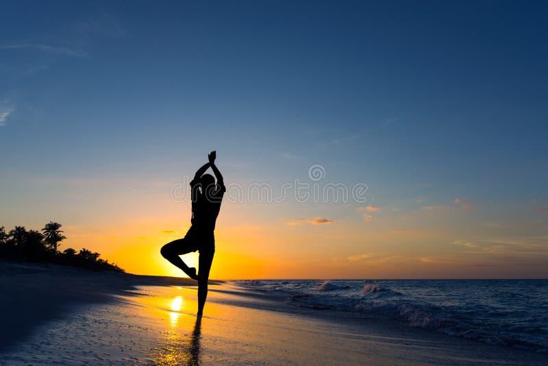 Pose d'arbre de vrikshasana de yoga par la femme en silhouette sur la plage avec le fond de ciel de coucher du soleil L'espace li images stock
