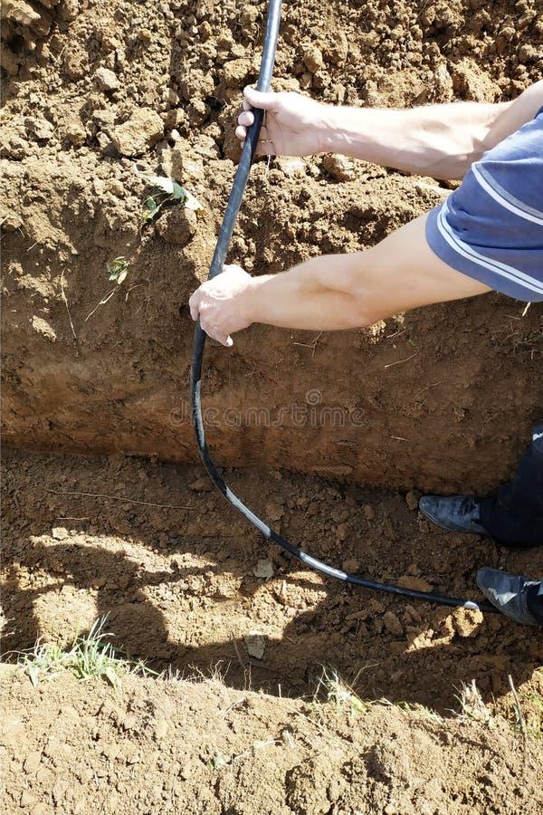 Pose d'un câble électrique dans la terre d'un électricien principal image libre de droits