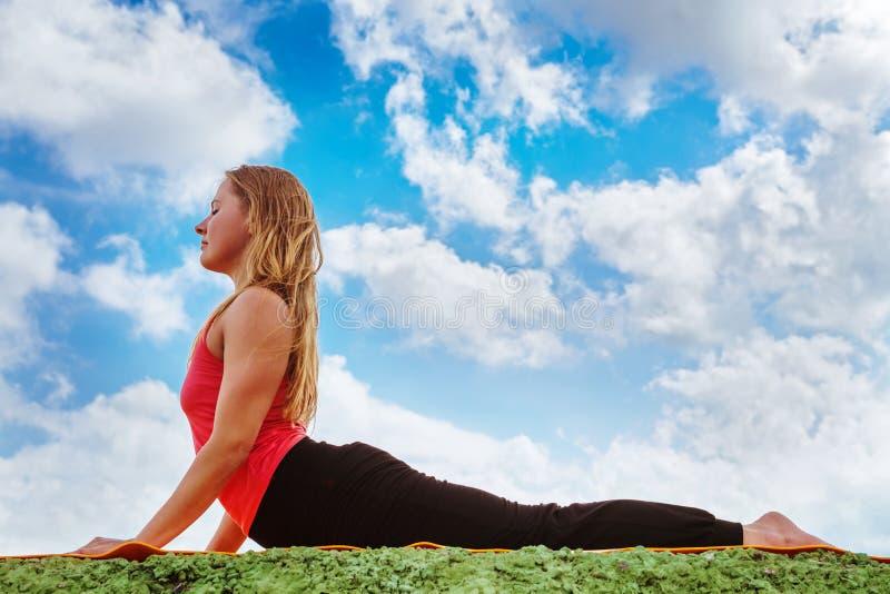Pose da ioga da cobra da mostra da jovem mulher perfeitamente imagem de stock