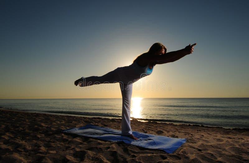 Pose da ioga do guerreiro III na praia imagens de stock royalty free