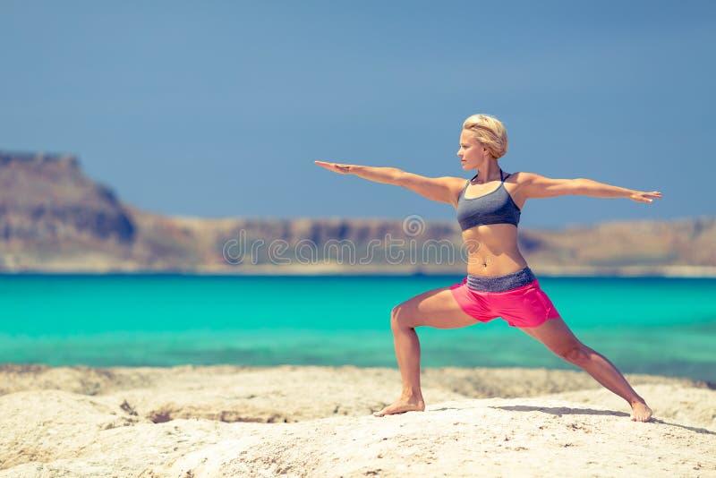Pose da ioga, exercício apto da mulher na praia imagens de stock royalty free