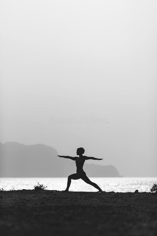 Pose da ioga, mulher que medita na praia imagem de stock royalty free
