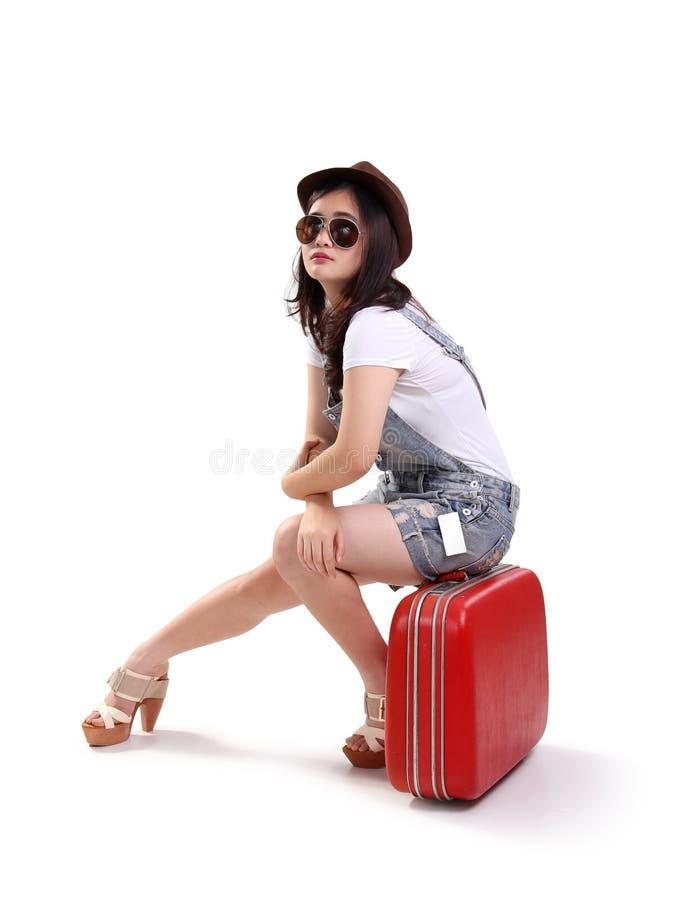 Pose da situação da mulher do viajante na mala de viagem vermelha isolada foto de stock