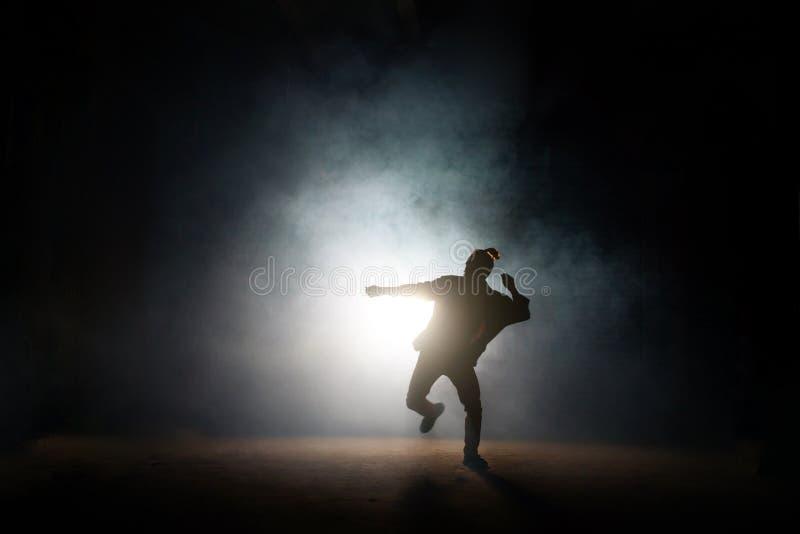 Pose de danse de mâle sur une jambe sur le fond foncé image libre de droits