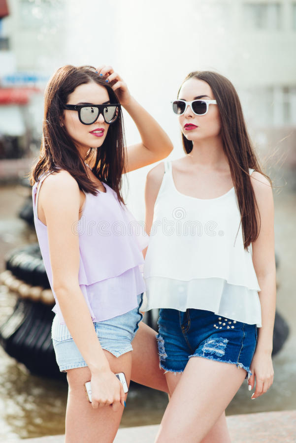 Pose de deux belle amies sur la rue photos stock
