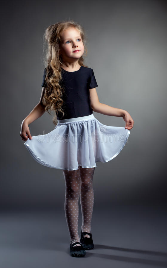 Pose de fille assez petite redressée sa jupe photographie stock libre de droits