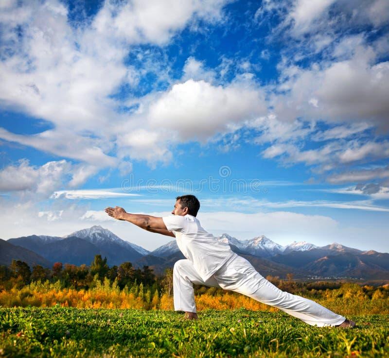 Pose de guerrier de yoga en montagnes photo libre de droits