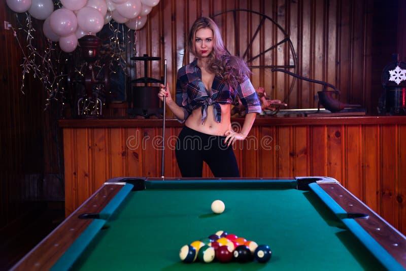 Pose de jeune femme sexy devant la table de billard de billard photo libre de droits