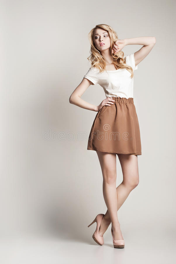 Pose de la femme blonde avec le long cheveu bouclé sur le blanc photos stock