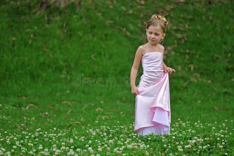 Pose de la fille dans la robe rose images stock