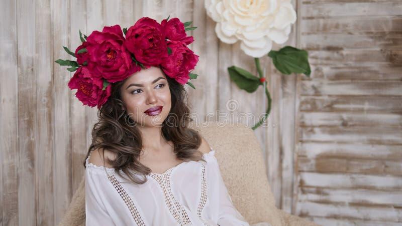 Pose de modèle de fille une jeune femme dans une guirlande des pivoines d'écarlate sur sa tête, de longs cheveux bouclés foncés d photo stock