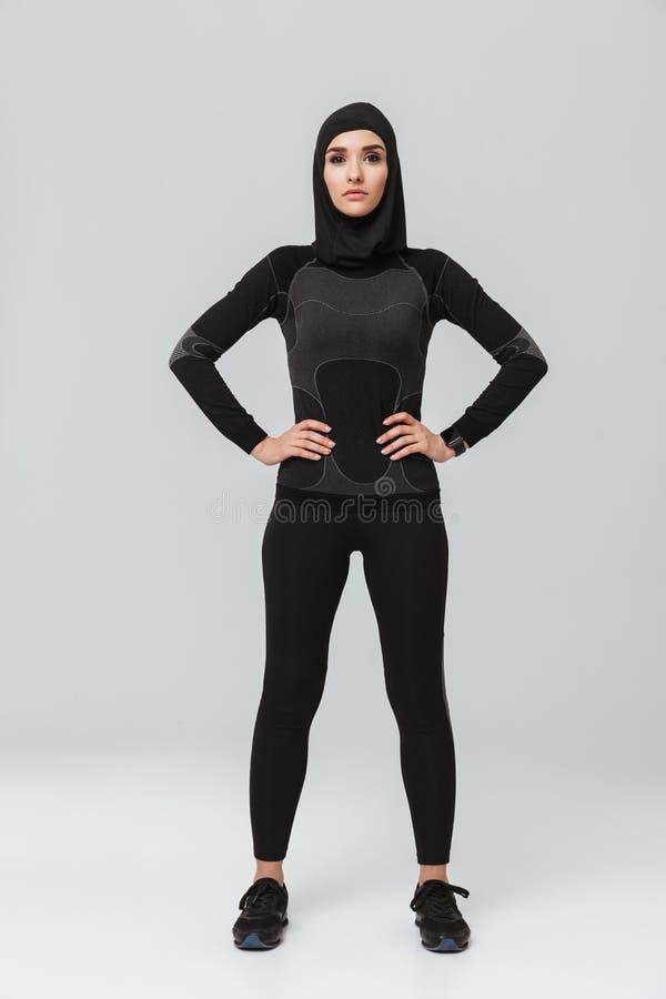 Pose de musulmans de forme physique de jeune femme d'isolement au-dessus du fond blanc de mur image stock