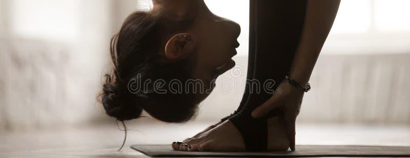 Pose de pratique d'uttanasana de femme horizontale d'image faisant l'exercice en avant de courbure images stock