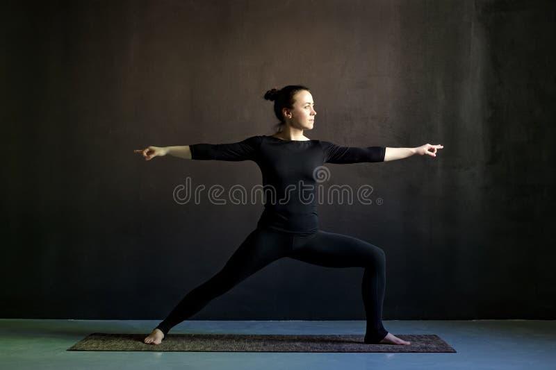 Pose de pratique de guerrier de yoga de jeune femme, Virabhadrasana images stock