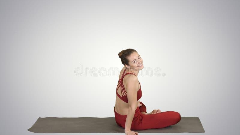 Pose de pratique de lotus de yoga de femme sportive, se tournant vers la caméra et souriant sur le fond de gradient photo stock