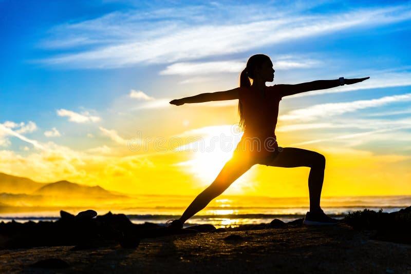 Pose de pratique de yoga du guerrier II de silhouette de forme physique photographie stock libre de droits
