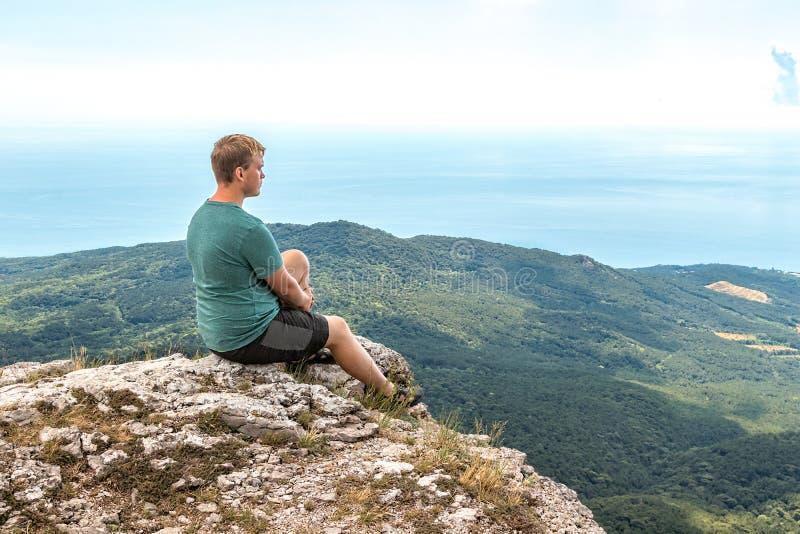Pose de pratique de yoga de jeune homme se reposant sur la crête rocheuse L'homme font la méditation et vue de apprécier photographie stock libre de droits
