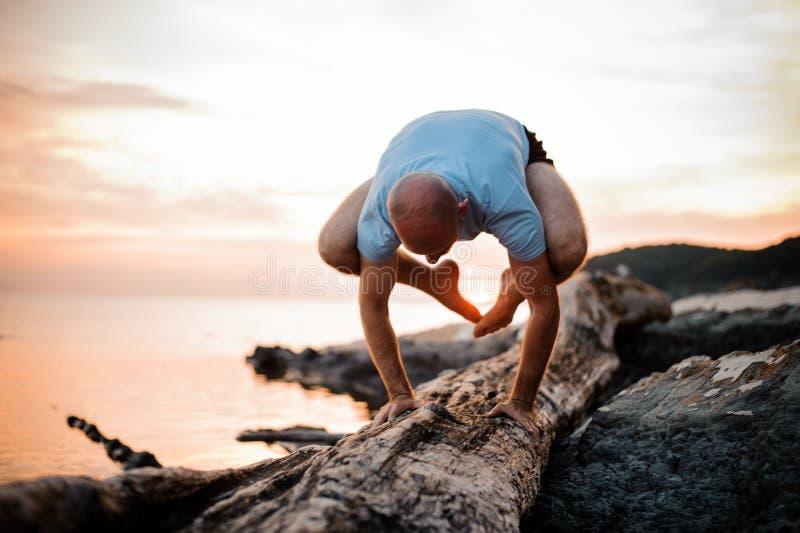Pose de yoga d'appui renversé par l'homme sur la plage près de l'océan image stock