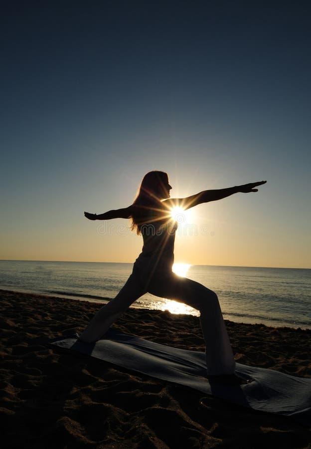 Pose de yoga du guerrier II sur la plage image libre de droits