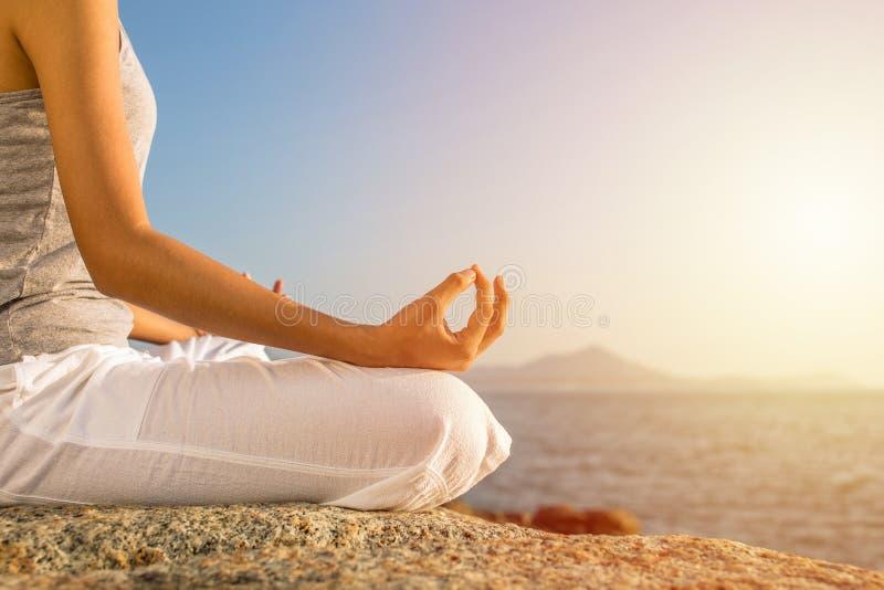 Pose de yoga de méditation de jeune femme sur la plage tropicale avec la lumière du soleil image stock