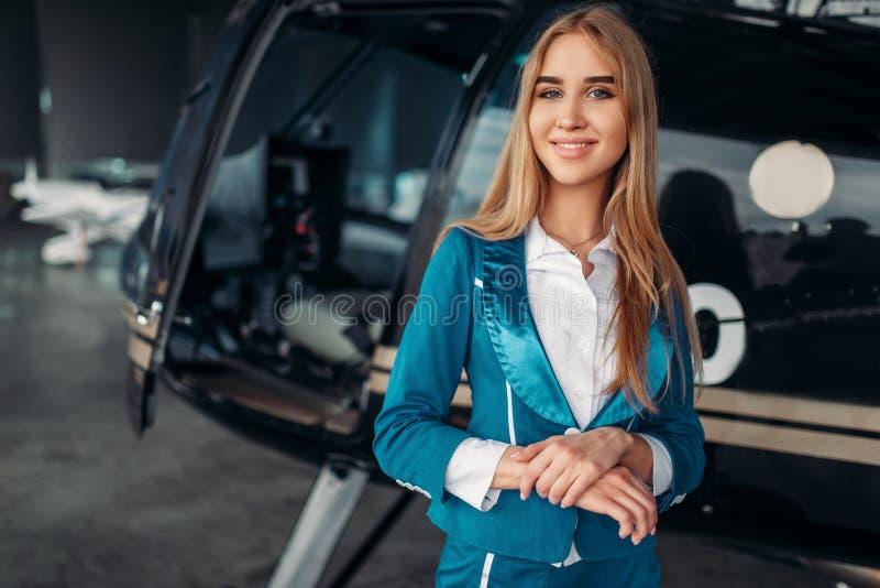 Pose dell'hostess contro l'elicottero in capannone fotografia stock libera da diritti