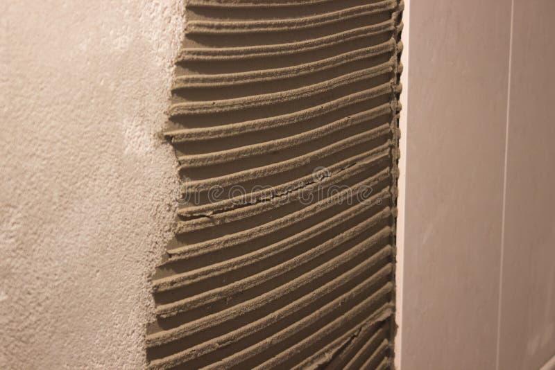 Pose des carreaux de céramique sur le mortier de ciment la distribution de la solution a figuré la spatule sur le mur processus f photos libres de droits