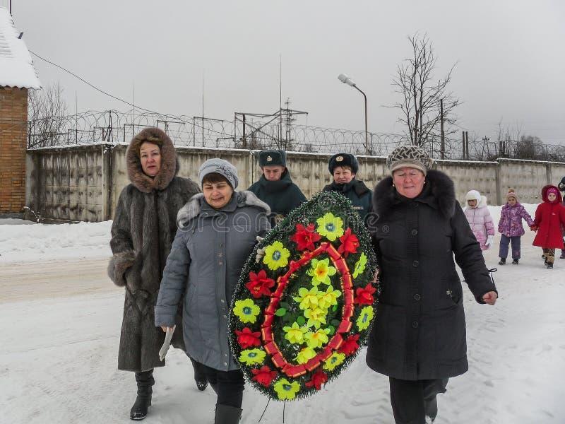 Pose des fleurs et des guirlandes d'enterrement à une tombe de masse dans la région de Kaluga en Russie photographie stock libre de droits