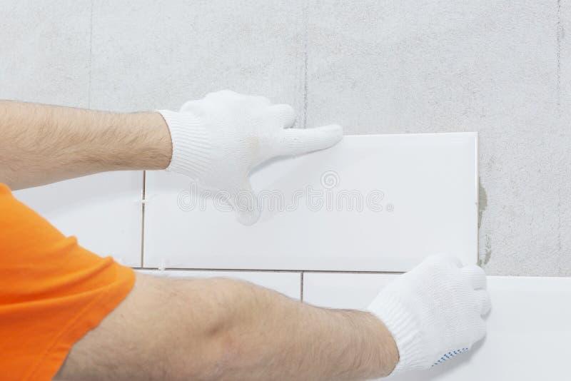 Pose des tuiles sur le mur avec des garnitures, travail de réparation photo stock