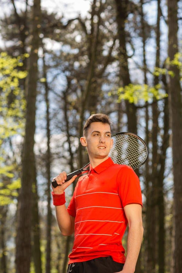 A pose do homem com uma raquete de t?nis e um par termoel?trico alaranjado, no fundo do parque verde Conceito do esporte imagens de stock