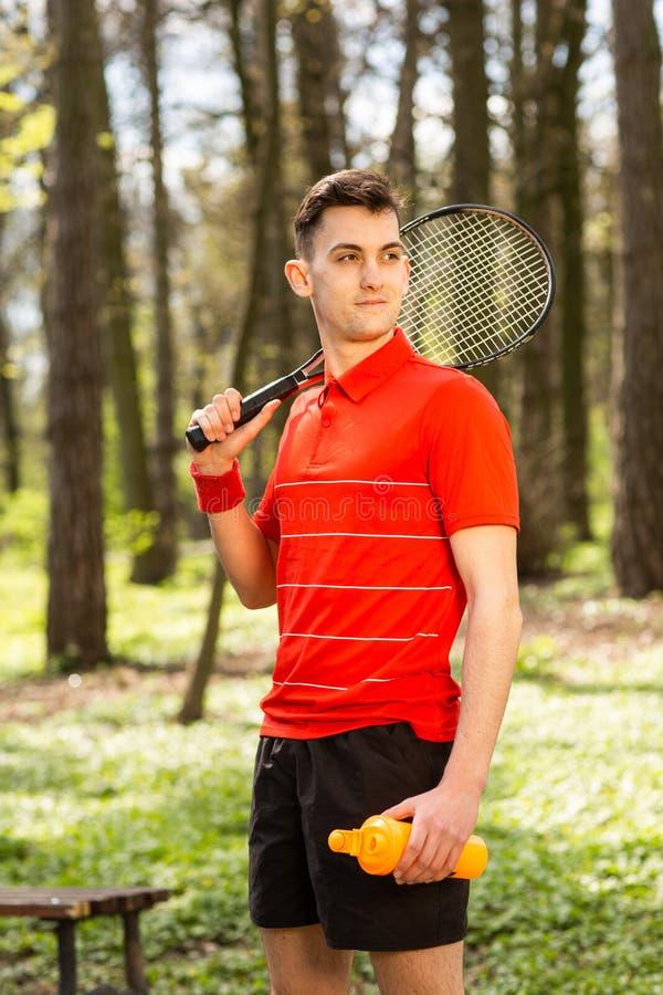 A pose do homem com uma raquete de t?nis e um par termoel?trico alaranjado, no fundo do parque verde Conceito do esporte imagens de stock royalty free