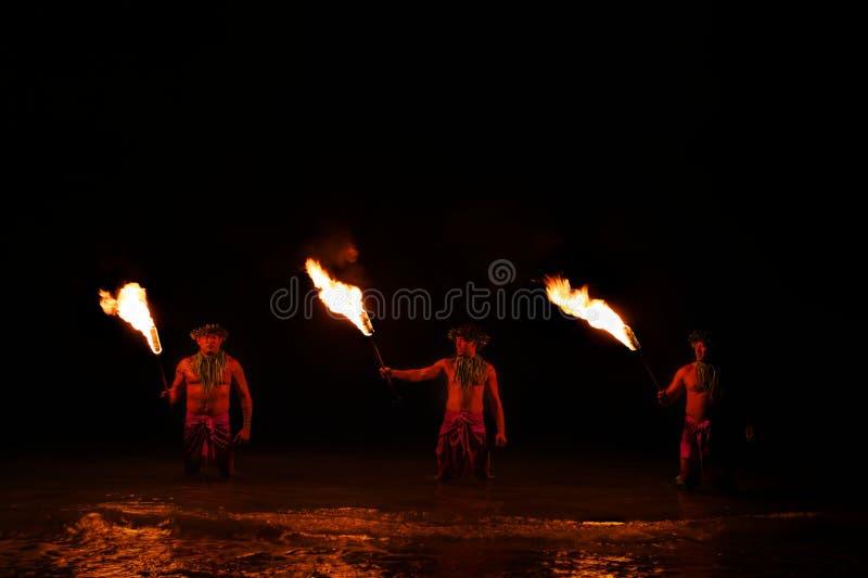 Pose dos dançarinos do fogo na água imagem de stock