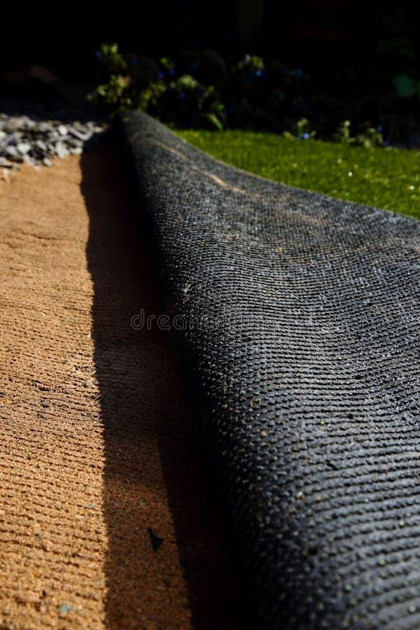 Pose du gazon artificiel d'herbe sur le sable photo stock