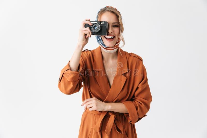 Pose en soie de port d'écharpe de belle jeune jolie femme blonde d'isolement au-dessus de la photographie blanche de caméra de pa image libre de droits