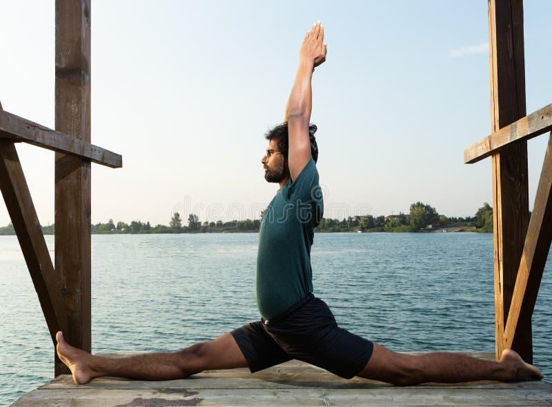 Pose fazendo mestra do macaco da ioga perto da água fotos de stock royalty free
