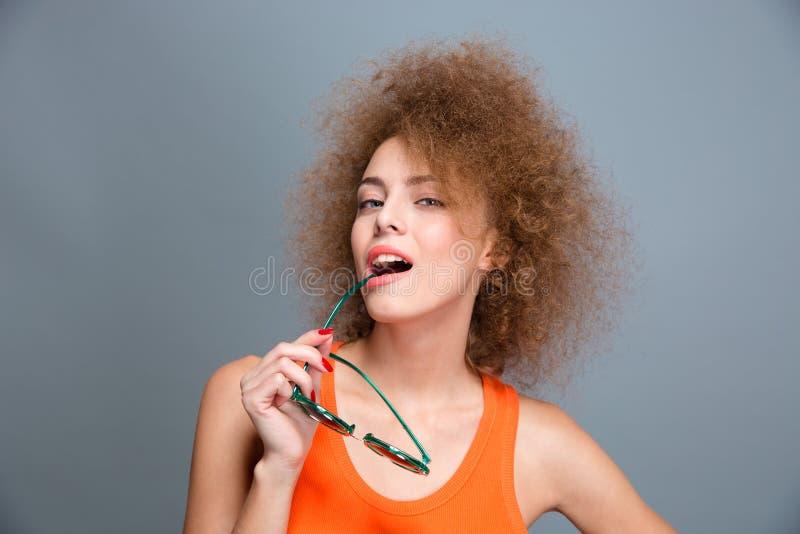 Pose femelle bouclée sûre espiègle avec des lunettes de soleil image stock