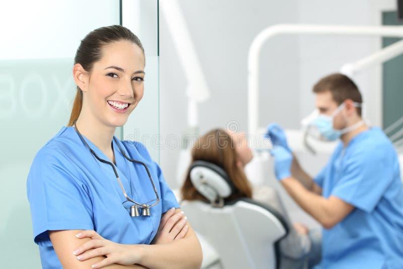Pose femelle de dentiste à la consultation images stock