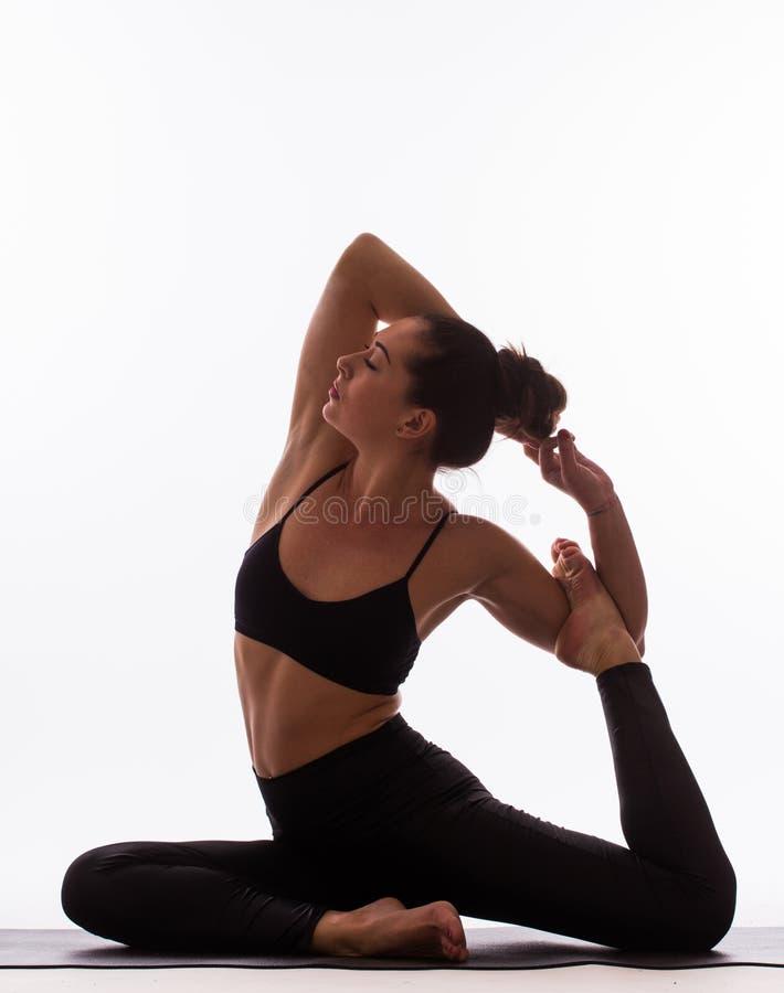 Pose femelle de jeune beau yoga sur un fond de studio photo libre de droits