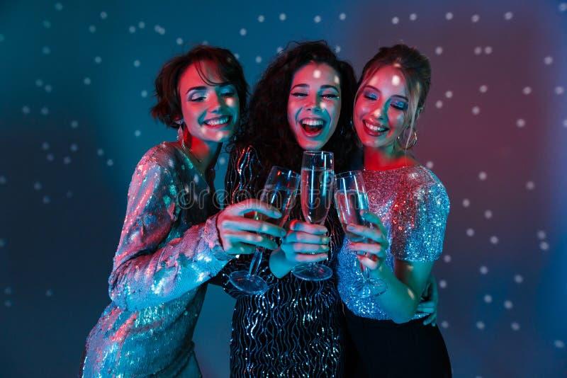 Pose heureuse de femmes d'isolement avec des lumières de boule de disco tenant des verres avec le champagne image stock