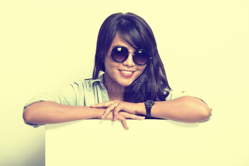 Pose heureuse de jeune femme avec le panneau d'affichage vide blanc image libre de droits