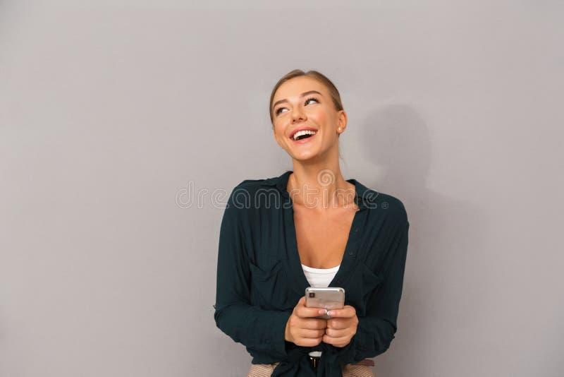 Pose heureuse de jeune femme d'affaires d'isolement au-dessus du fond gris de mur utilisant le téléphone portable image libre de droits
