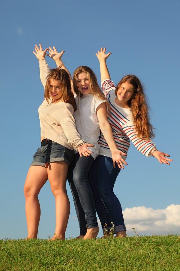 Pose heureuse de trois filles à l'herbe verte photographie stock libre de droits
