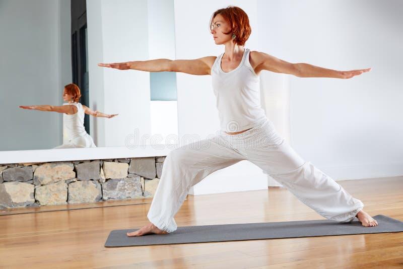 Pose II du guerrier deux de yoga dans le plancher en bois images stock