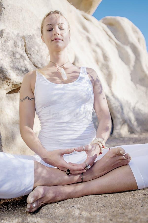 Pose méditante de yoga de femme de yoga de désert images stock