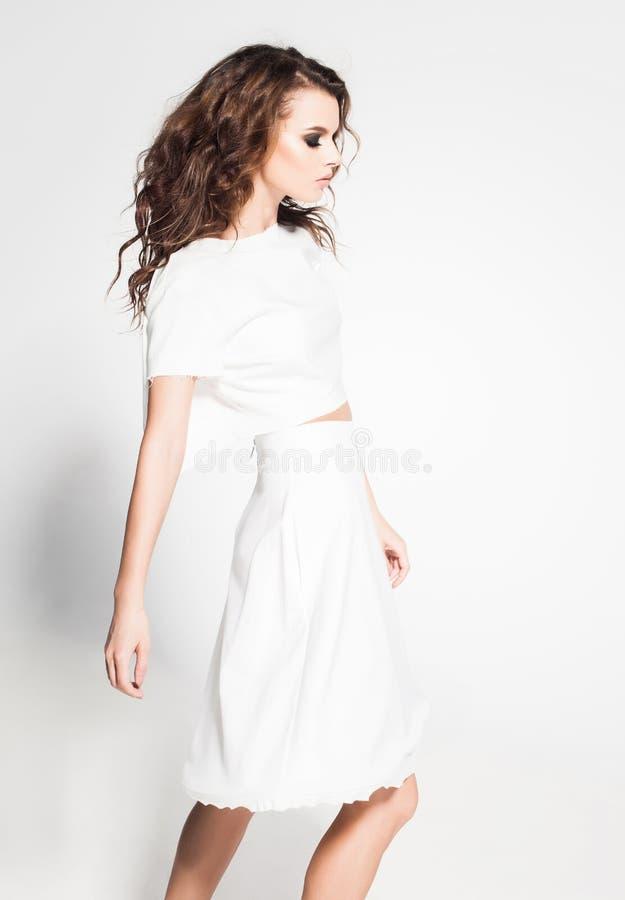 Pose modèle de belle femme dans la robe blanche dans le studio photo stock