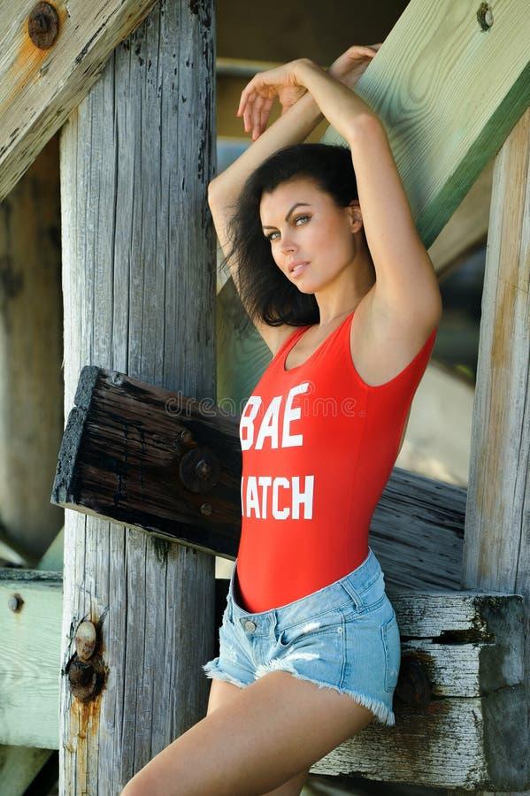 Pose modèle de brune attrayante dans le maillot de bain rouge à la mode et shorts sur la plage images libres de droits