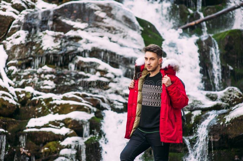 Pose modèle de type près de la cascade en montagnes d'hiver photographie stock