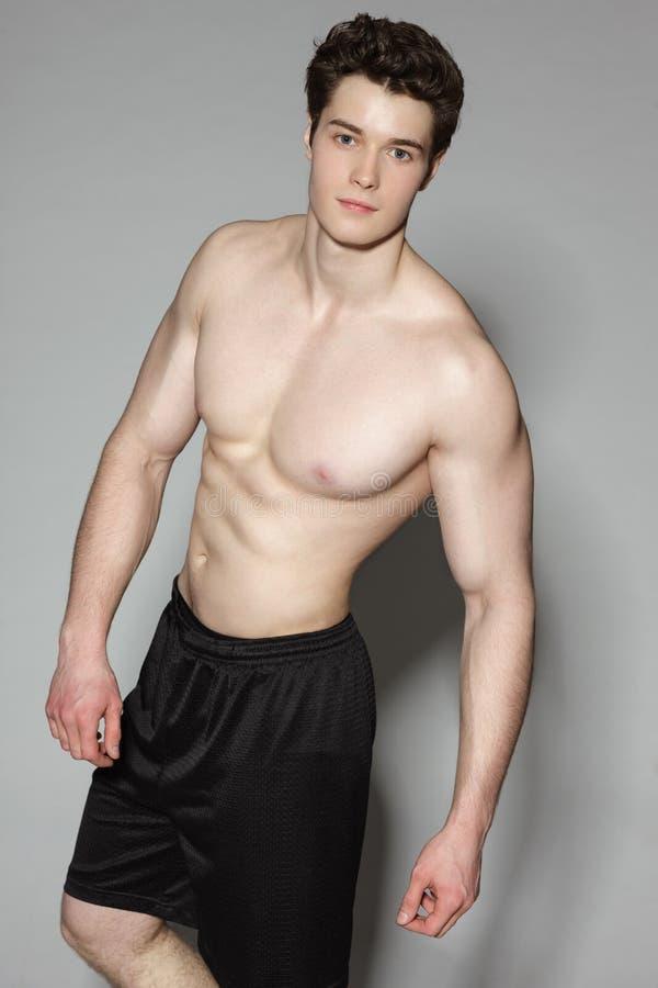 Pose musculaire de sportif sans chemise photos stock