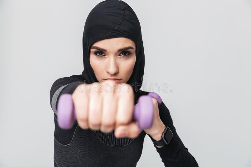 Pose musulmane de boxeur de combattant d'isolement au-dessus du fond blanc de mur pour faire des exercices avec des haltères photo stock