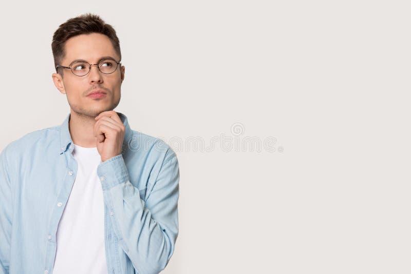 Pose pensativa pensativa do homem novo no fundo cinzento que olha de lado imagens de stock
