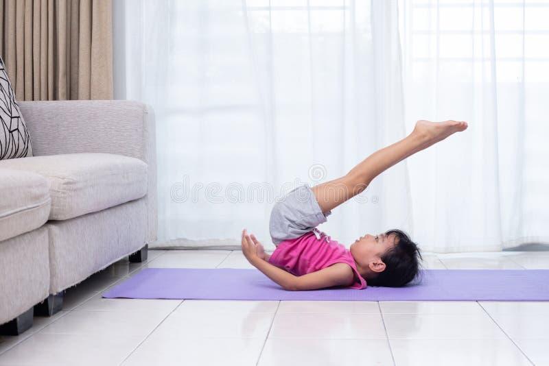 Pose praticando da ioga da menina chinesa asiática em uma esteira imagens de stock royalty free